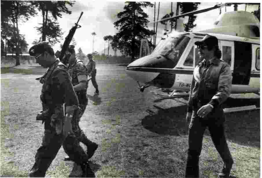 Geraldo walks past the helicopter with local troops, circa 1970