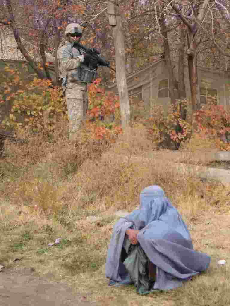 Soldier examines local sitting and wearing hijab