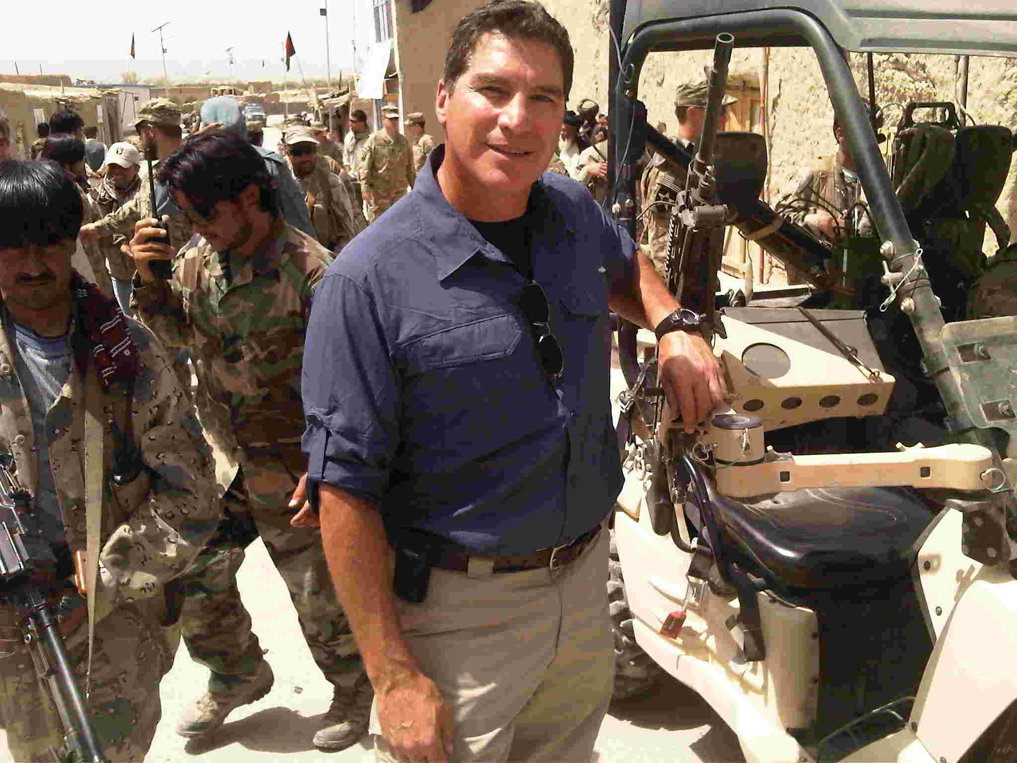Field Correspondent Craig Rivera in the midst of local troops and equipment