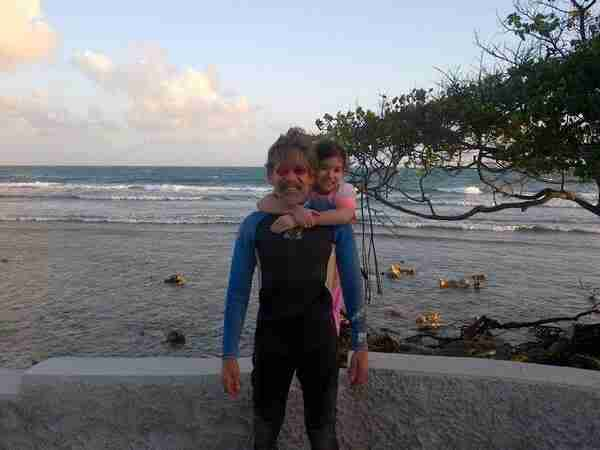 Geraldo in a wet suit with his youngest daughter Sol on island Salinas, Puerto Rico