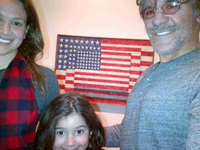Geraldo with his wife Erica and their daughter sol appreciate the American Flag, artistically.