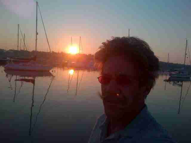 Geraldo with the setting sun, in a peaceful harbor on board sailing vessel Voyager.