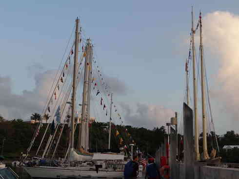 Sailing vessels with their flags up in front of the Royal Hamilton Amateur Dinghy Club, after the Marion to Bermuda race in 2013.