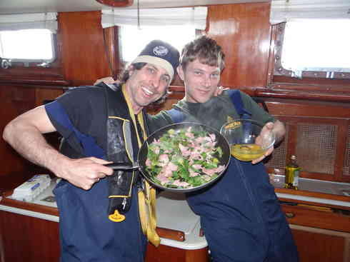 Crew members Greg and Forrest prep lunch while Voyager makes way, during the Marion to Bermuda race 2013.