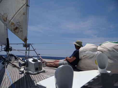 Crew member Ross catches some sun on the bow of Voyager, during Marion to Bermuda race in 2013.