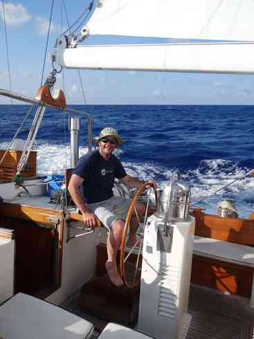 Crew member Ross at the helm of Voyager during the 2013 Marion to Bermuda sailing race.