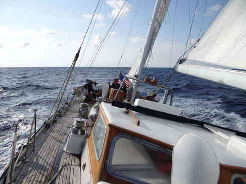 Voyager heeled over with the crew on the aft deck.  Taken during the 2013 Marion to Bermuda sailing race.