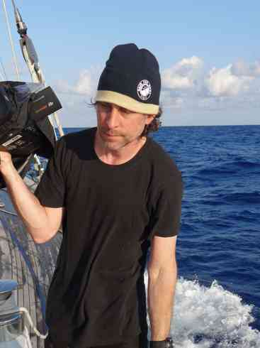 Crew member and producer Greg stands with camera at the ready on board Voyager.  Marion to Bermuda sailing race, 2013.
