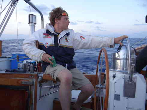 Crew member Forrest at the helm of Voyager during a dawn watch.  Marion to Bermuda sailing race, 2013.