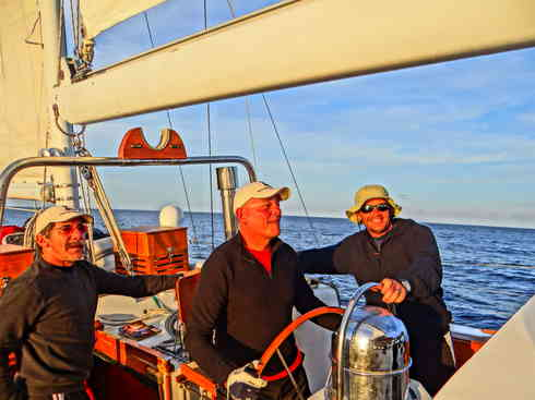 The mornings sun falls on Voyagers' crew during first watch.  From left are Geraldo, Dr. Guillermo, and Ross.  Marion to Bermuda sailing race, 2013.