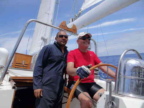 Voyager crew members Kevin (left) and Dr. Guillermo at the helm during 2013 Marion to Bermuda sailing race.