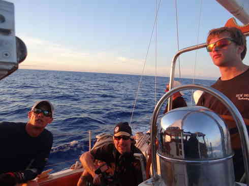 Voyager crew catches the last few rays of light.  From left; Larry, Greg, Forrest at the helm.  Marion to Bermuda sailing race 2013.