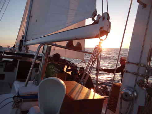 Crew members in the cockpit as the first bits of light break over Voyager.  Marion to Bermuda sailing race, 2013.