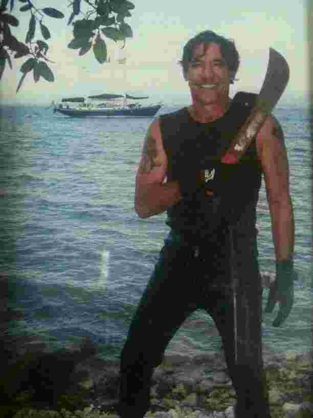 Geraldo with a machete after swimming ashore an island in Puerto Rico, sailboat Voyager in the background.
