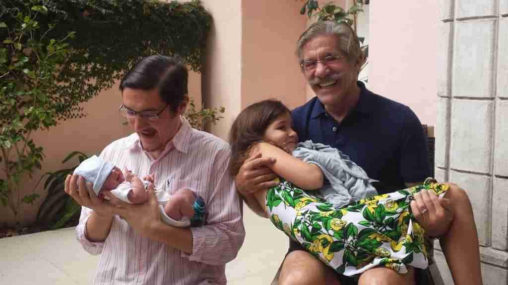 Geraldo carries his youngest daughter Sol while visiting his oldest son Gabriel, and new grandson Desi.