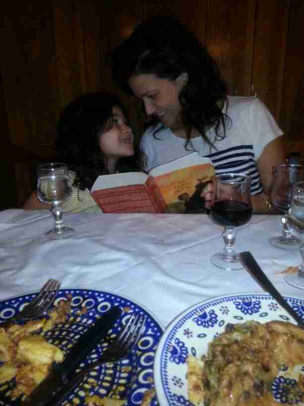 Wife Erica reads with youngest daughter Sol after a meal.