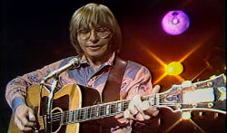 John Denver plays guitar